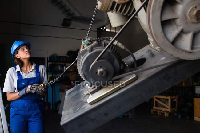 Mujer mecánico utiliza un polipasto para levantar el motor compresor garaje - foto de stock