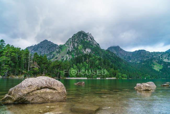 Stones on mountain lake shore — Stock Photo