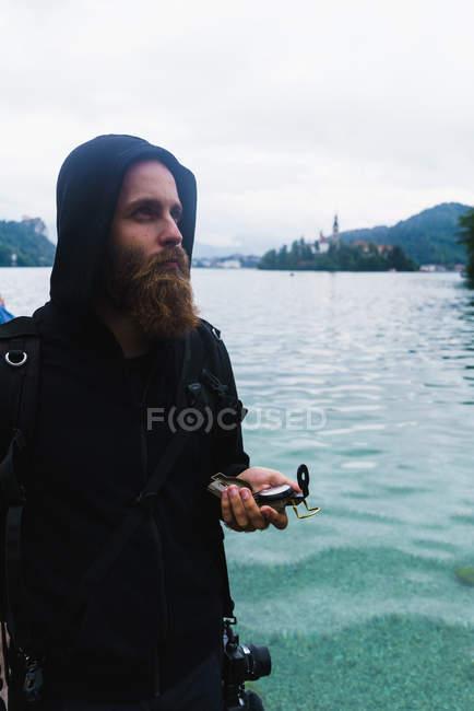 Uomo barbuto che tiene la bussola — Foto stock