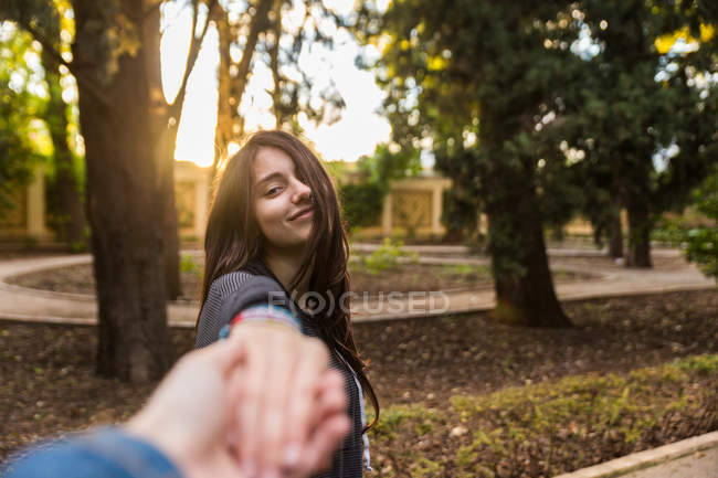 Pretty young girl looking at camera and gesturing follow me with photographer's hand. — Stock Photo