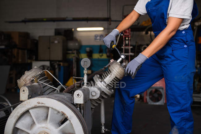 Low section of female mechanic fixing  compressor engine with wrench — Stock Photo