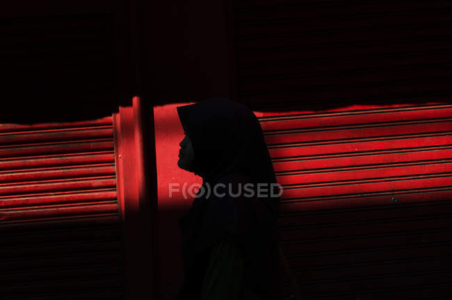 Silhouette of woman wearing headscarf on background of red shutters — Stock Photo
