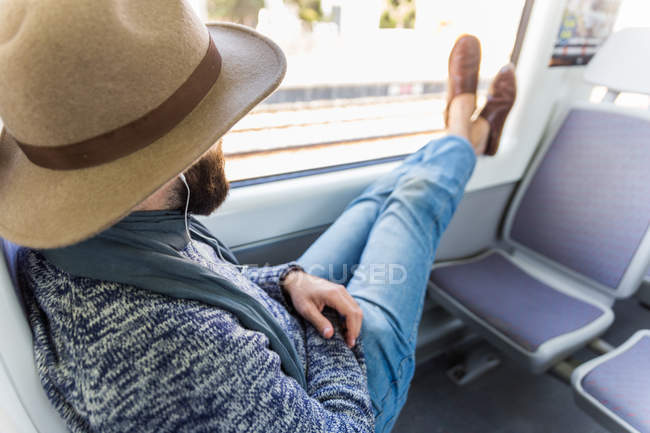 Side view of bearded man in hat putting legs on window and relaxing in train. — Stock Photo