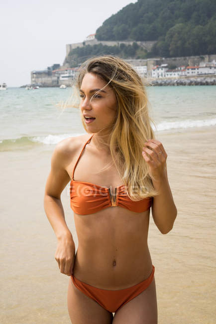 Slim girl in bikini posing on beach — Stock Photo