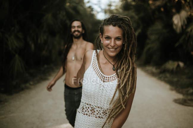 Портрет усміхається жінка з дреди проведення mans руку і дивлячись на камеру в тропічних road серед пальм — стокове фото