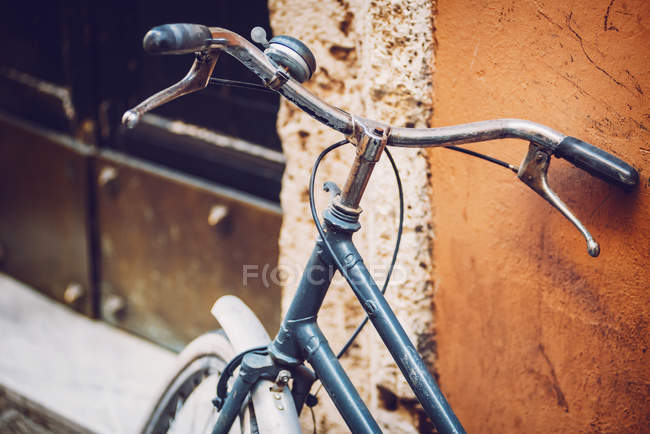 Crop image of bike leaned on old wall at street scene — Stock Photo