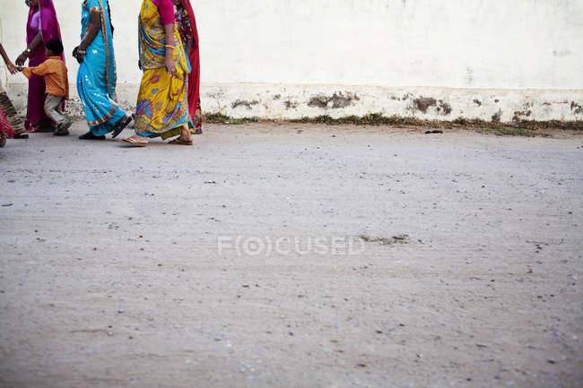 Обтинання жінки носять барвисті Сарі йшов по вулиці з дитиною. — стокове фото