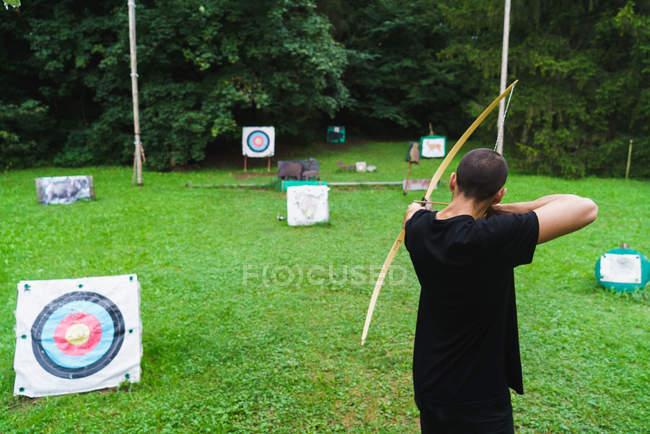 Человек, практикующий стрельбу из лука на лужайке — стоковое фото