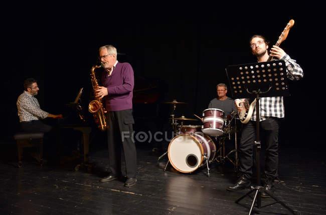 Группа музыкантов, играющих на сцене в свете софитов — стоковое фото