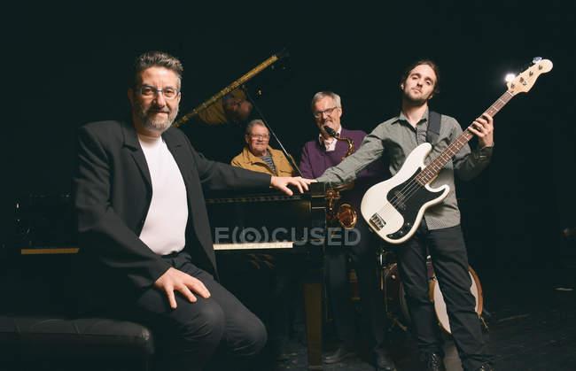 Grupo de hombres de diferentes edades posando con diferentes instrumentos en el escenario - foto de stock