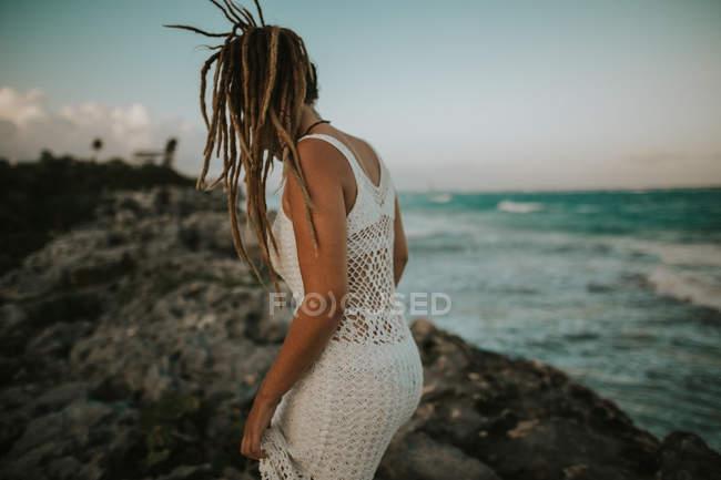 Rear view of woman with dreadlocks wearing white crochet dress woman walking on rocks at ocean coast — Stock Photo