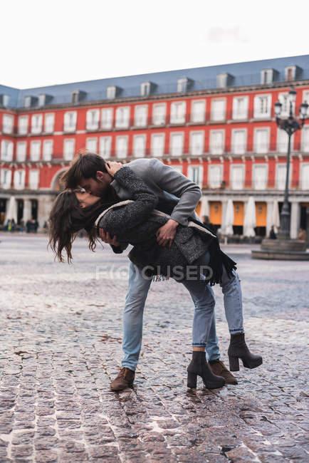 Молоді коханці, даючи Пристрасний поцілунок на площі міста — стокове фото