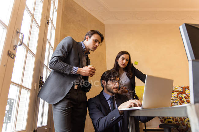 Group of people in suits attentively watching in laptop. — Stock Photo