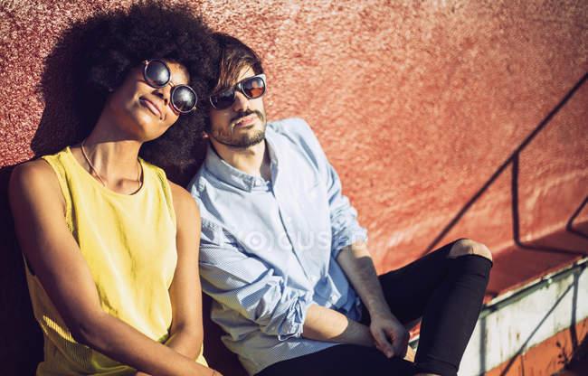 Міжрасові пари в сонцезахисні окуляри, сидячи за стіни і дивлячись на камеру — стокове фото