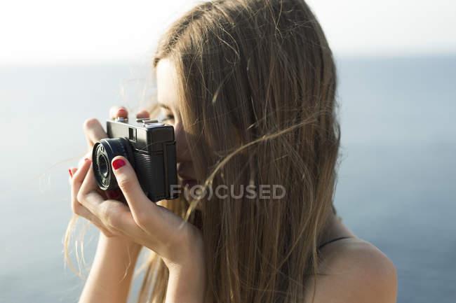 Jeune fille brune prenant tourné avec la caméra analogique — Photo de stock
