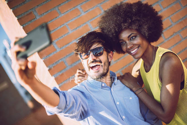 Cheerful interracial couple taking selfie against brickwall — Stock Photo