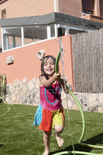 Mädchen spielt an heißen Sommertagen mit Schlauch im Garten — Stockfoto