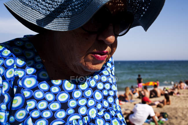 BARCELONA, SPAIN - 10 July, 2011: Portrait of senior woman wearing hat and sunglasses on background of beach and sea. — Stock Photo