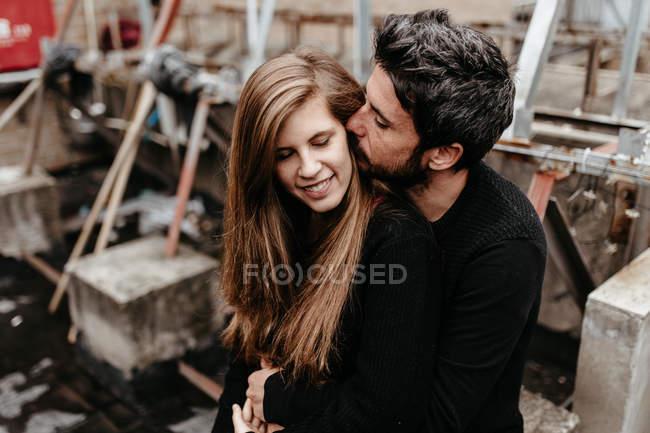 Bearded uomo abbracciare bionda ragazza da dietro e baciare orecchio . — Foto stock