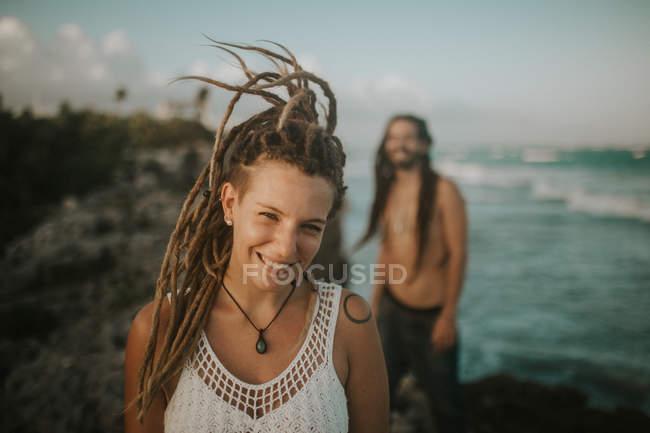 Портрет посміхається дівчина з дреди, дивлячись на камери над людиною постановки на тропічний пляж гальковий — стокове фото