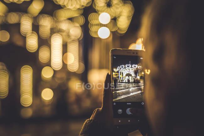 Через плечо вид женщины, снимающей карусель на смартфон . — стоковое фото
