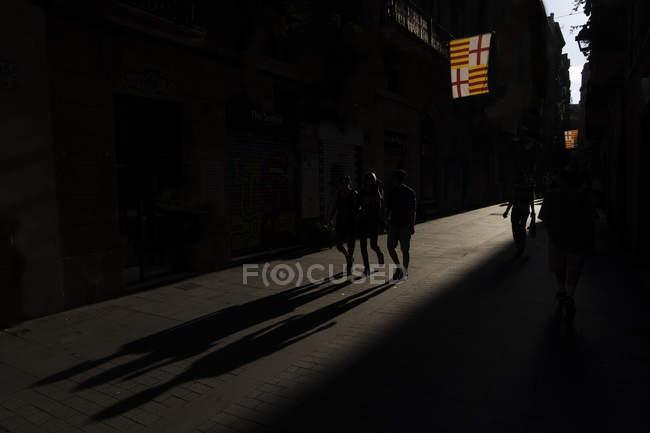 Persone che camminano nel vicolo della città con la luce del sole facendo lunghe ombre . — Foto stock