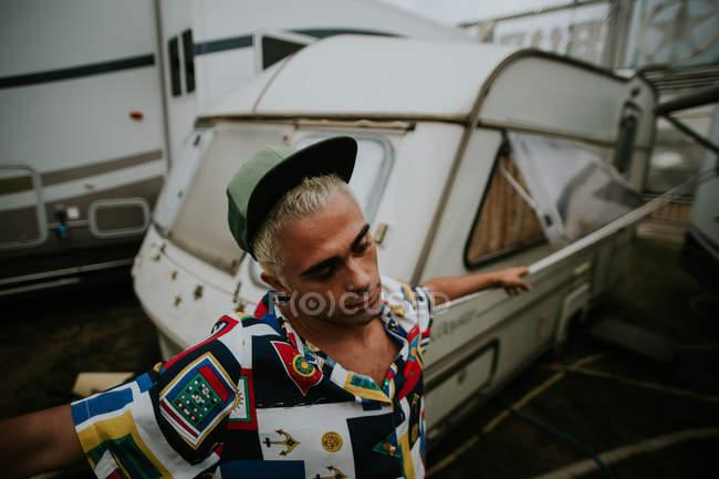 Homme avec des cheveux décolorés posant contre remorque — Photo de stock