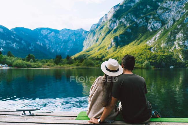 Пара сидящих у горного озера — стоковое фото