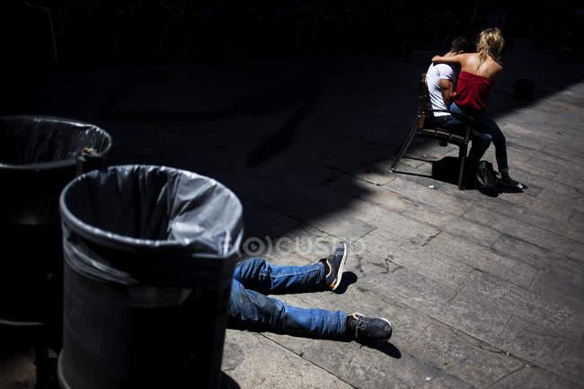 Анонімні пара, сидячи на стільці в кімнаті з тілом, що лежить за барелів. — стокове фото