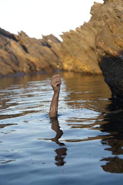 Рука з ігристого світло, що стирчить з спокійне озеро з рок — стокове фото