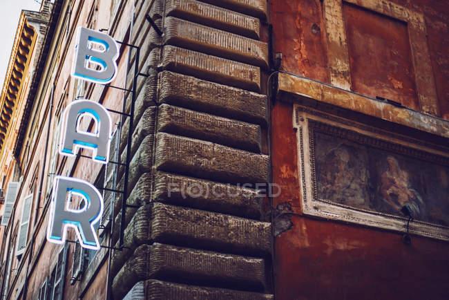 Unteransicht des Gebäude Ecke mit bar Zeichen auf Fassade mit kunstvollen alten Gemälde — Stockfoto
