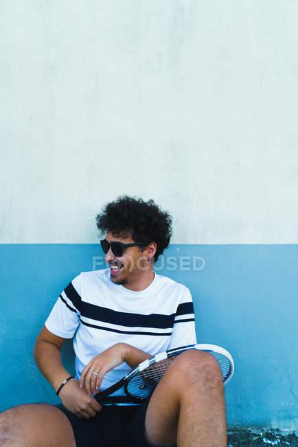Hombre alegre con raqueta sentado junto a la pared y mirando a un lado - foto de stock