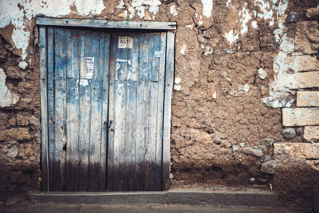 Old rough door inrural shabby wall — Stock Photo