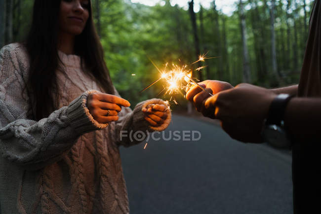 Couple with sparklers in woods — Stock Photo