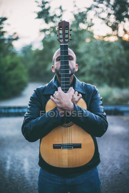 Mann küsst Flamenco-Gitarre in der Natur — Stockfoto