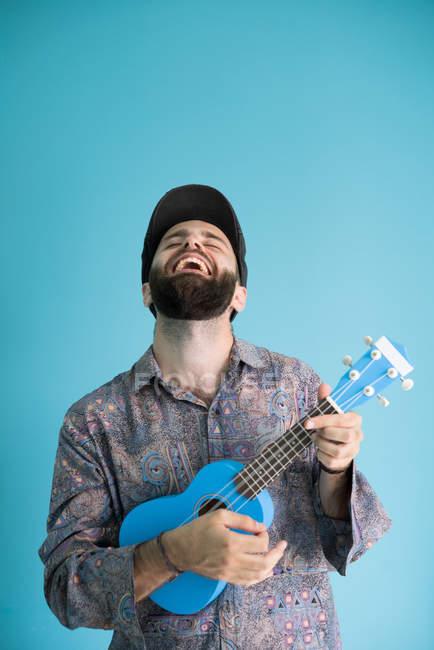 Lachender bärtiger Mann spielt traditionelle Ukulele-Gitarre auf blauem Hintergrund — Stockfoto