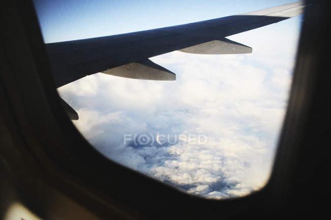 Ala de avião no fundo do céu nublado . — Fotografia de Stock