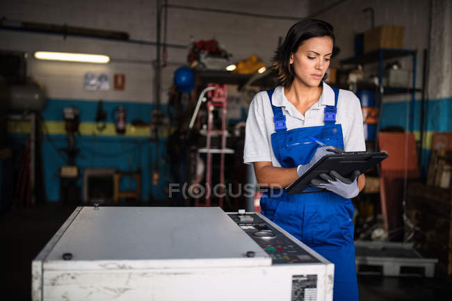 Female mechanic using tablet computer in garage — Stock Photo