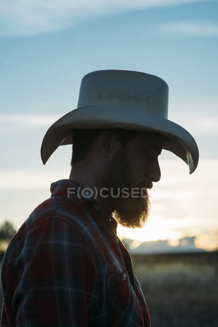 9e007d13e05 Side view of bearded man in cowboy hat posing at countryside in dusk —  Stock Photo