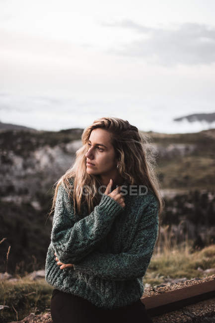 Blonde woman sitting at roadside over landscape — Stock Photo