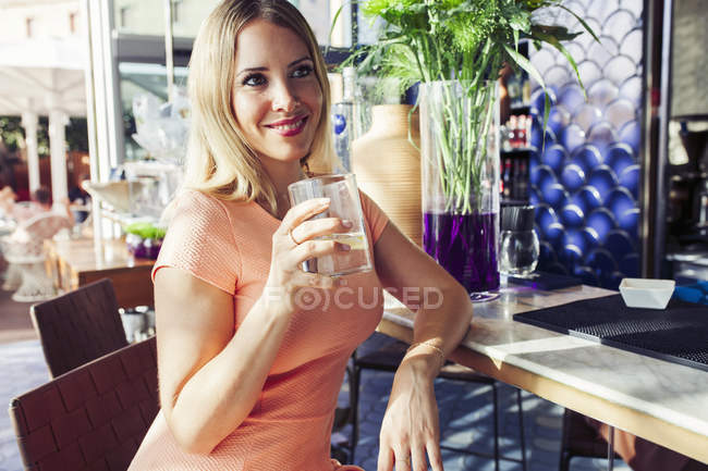 Woman with glass of refreshing drink and sitting at counter — Stock Photo