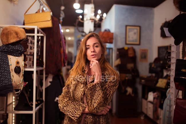 Молодий стильна дівчина у постановці в шубу на фоні одяг кімната. — стокове фото
