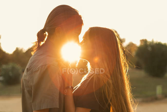 Portrait of couple embracing and looking face to face at sunset — Stock Photo