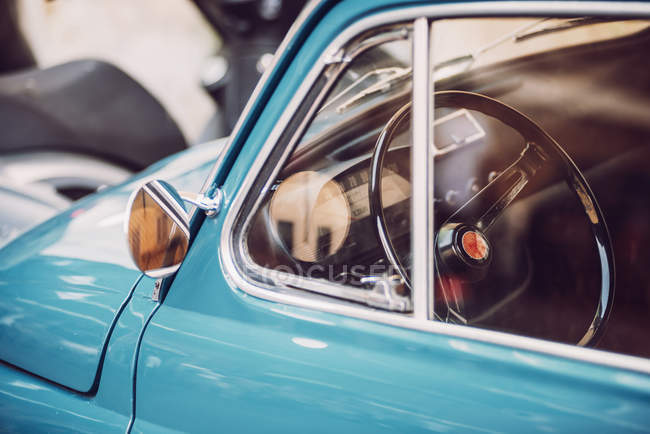 Crop image of blue vintage car at street scene — Stock Photo