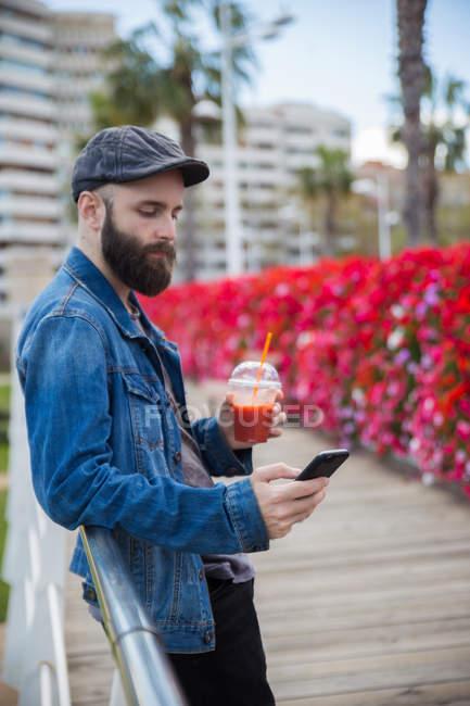 Vue latérale de l'homme barbu appuyé sur la main courante avec smoothie à la main et smartphone de navigation — Photo de stock