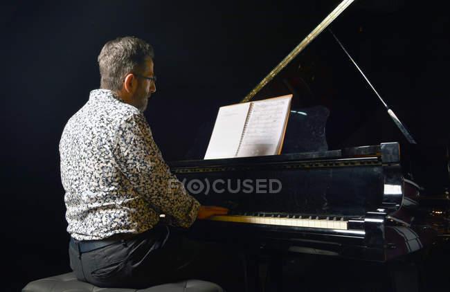 Старший мужчина, играть на пианино на стадии — стоковое фото