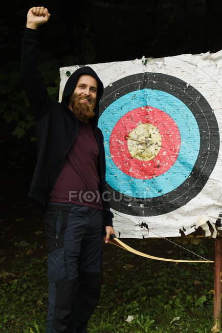 Молодой бородатый мужчина, держа лук и триумфально стоя рядом со стрелой в центре цели . — стоковое фото