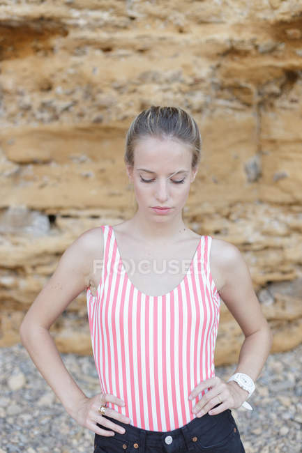 Portrait of young blonde girl in striped shirt posing over sandstone wall and looking down — Stock Photo