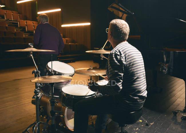 Rückansicht eines Mannes, der auf der Bühne Schlagzeug spielt — Stockfoto