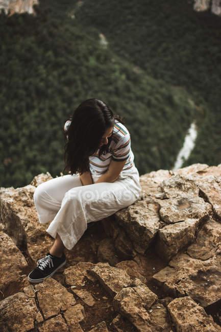 Mulher sentada na pedra e olhando para baixo — Fotografia de Stock